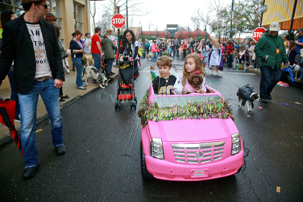 """23 Feb 2014. New Orleans, Louisiana.<br /> Lucy Walker(7 yrs), her brother Everett (5 yrs) and dog Lilly on the wet and soggy streets of the French Quarter at the 22nd Mystic Krewe of Barkus parade, the only officially licensed Mardi Gras krewe by and for canines. This year's parade is themed  """"Dogzilla: Barkus Licks the Crescent City."""" <br /> Photo; Charlie Varley/varleypix.com"""