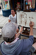 Young man has his portrait drawn by a man selling his skills. Brighton, East Sussex.