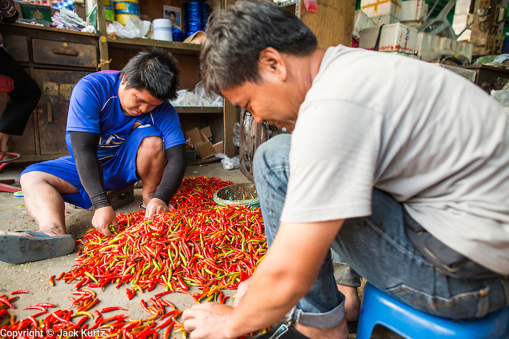 """06 MARCH 2013 - BANGKOK, THAILAND:  Men sort chilies in a market in Bangkok. Thailand's economic expansion since the 1970 has dramatically reduced both the amount of poverty and the severity of poverty in Thailand. At the same time, the gap between the very rich in Thailand and the very poor has grown so that income disparity is greater now than it was in 1970. Thailand scores .42 on the """"Ginni Index"""" which measures income disparity on a scale of 0 (perfect income equality) to 1 (absolute inequality in which one person owns everything). Sweden has the best Ginni score (.23), Thailand's score is slightly better than the US score of .45.  PHOTO BY JACK KURTZ"""