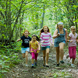 Five girls run on a forest trail at the Pell Farm in Grafton, Massachusetts.