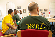 Prisoners attend an education meeting in Her Majesty's Prison Pentonville, London, United Kingdom.  They are part of the Doing Time Programme, one male wears the green Insider t-shirt which shows that he is a trusted inmate who offers support to other prisoners.