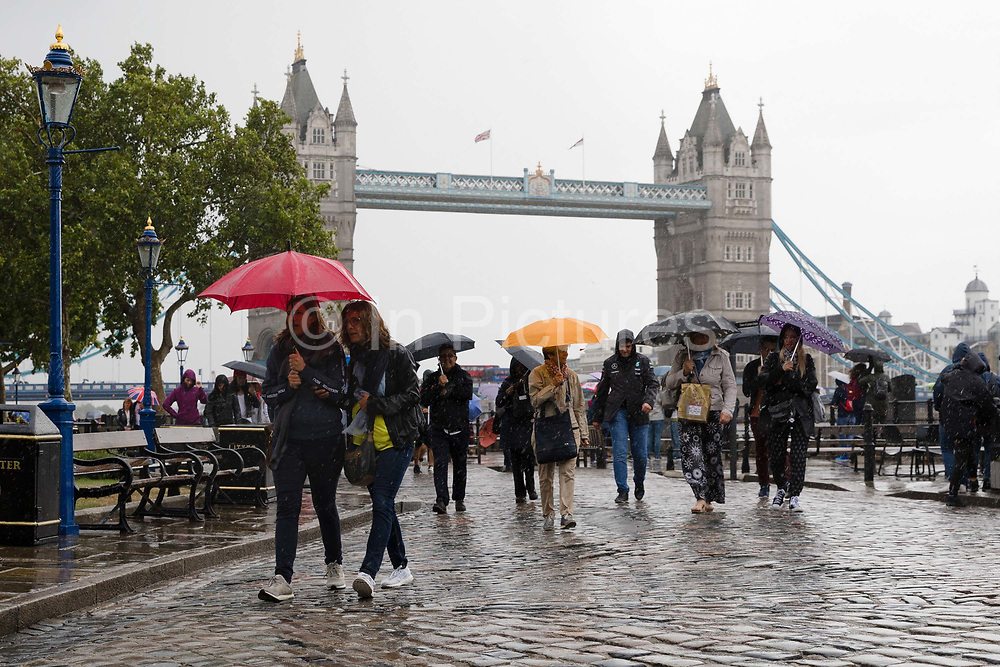 Tourists with umbrellas walking near Tower Bridge during rain and wet weather in London, England on August 10, 2018