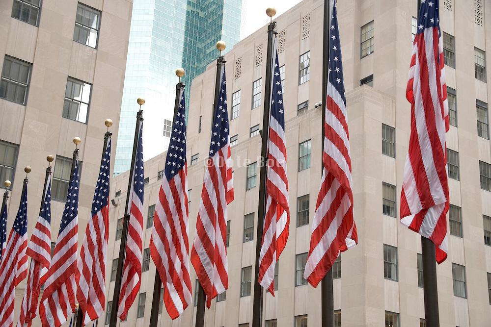 row of American flags at the Rockefeller center in New York City