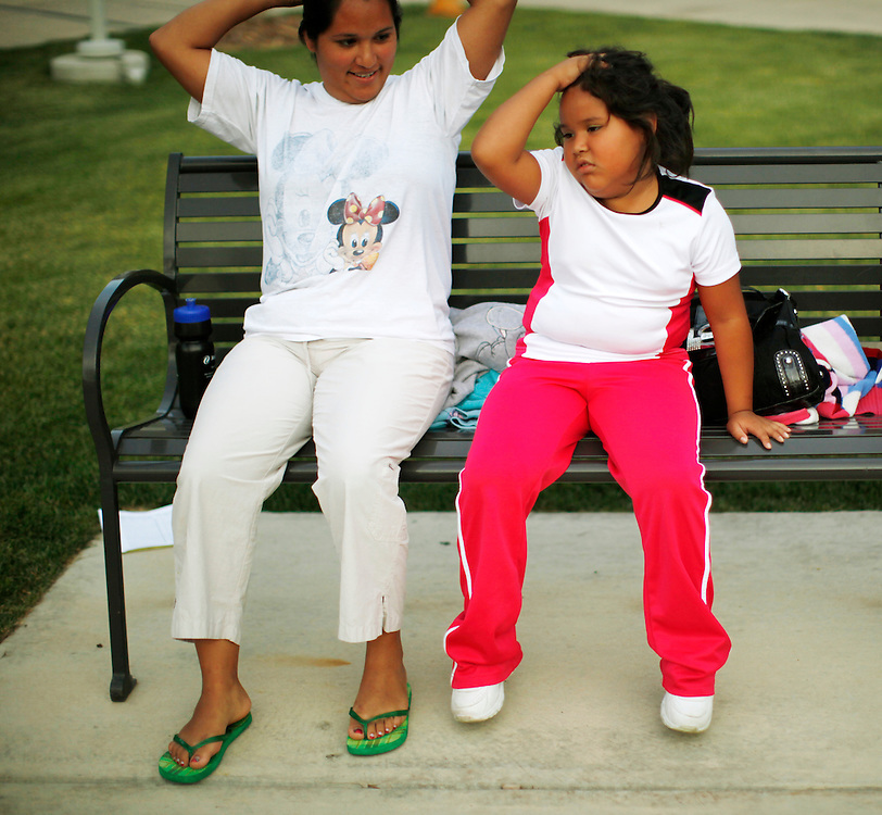 Fernanda Garcia-Villanueva, 8, (R) rests with her mother Areli Villanueva after exercising in the Shapedown Program at The Children's Hospital in Aurora, Colorado July 8, 2010.  Shapedown is part of the child and teen weight management programs at the hospital.  REUTERS/Rick Wilking (UNITED STATES)
