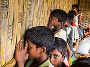 06 NOVEMBER 2014 - SITTWE, RAKHINE, MYANMAR: Rohingya Muslim boys watch a movie through holes in the palm frond walls of the theater in a Rohingya Muslim IDP camp near Sittwe. After sectarian violence devastated Rohingya communities and left hundreds of Rohingya dead in 2012, the government of Myanmar forced more than 140,000 Rohingya Muslims who used to live in and around Sittwe, Myanmar, into squalid Internal Displaced Persons camps. The government says the Rohingya are not Burmese citizens, that they are illegal immigrants from Bangladesh. The Bangladesh government says the Rohingya are Burmese and the Rohingya insist that they have lived in Burma for generations. The camps are about 20 minutes from Sittwe but the Rohingya who live in the camps are not allowed to leave without government permission. They are not allowed to work outside the camps, they are not allowed to go to Sittwe to use the hospital, go to school or do business. The camps have no electricity. Water is delivered through community wells. There are small schools funded by NOGs in the camps and a few private clinics but medical care is costly and not reliable.    PHOTO BY JACK KURTZ