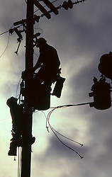 Stock photo of a silhouette of tow men making repairs at the top of a power pole