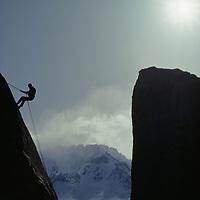 A rock climber rappels from boulder in Buttermilk Rocks.