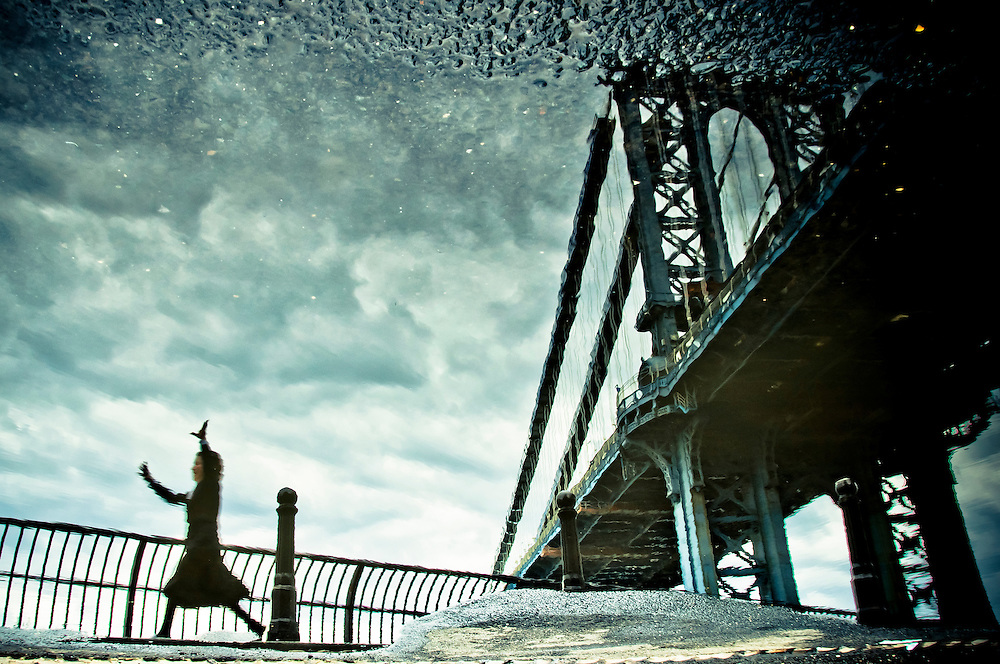 A girl runs down the Manhattan Bridge as seen in the reflection of a puddle in DUMBO, Brooklyn, New York.