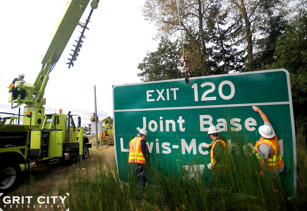 Washington State Department of Transportation employees Scott Davis, left, Russ Hinzpeter and Brandon Hilzer clean a new 10x15 foot Joint Base Lewis-McChord highway sign Monday prior to installing it at the Lewis Main exit along Interstate 5.