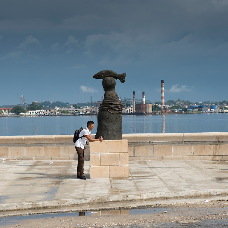 Havana, Cuba - October 2015: A young man waits the bus on Avenida del Puerto in central Havana. The Cuban government envisions a redevelopment of the historic waterfront. But decades of pollution have plagued the waters of the Caribbean sea into which it flows, making its cleansing a priority.