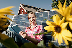 Woman leaning on solar panel reading book