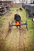 Amish man pushes a buggy ready for auction during the Annual Mud Sale to support the Fire Department  in Gordonville, PA.
