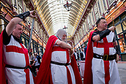 Three medieval knights spend lunchtime on St George's Day in Leadenhall Market in the capital's financial district (aka The Square Mile), on 23rd April, City of London, England.