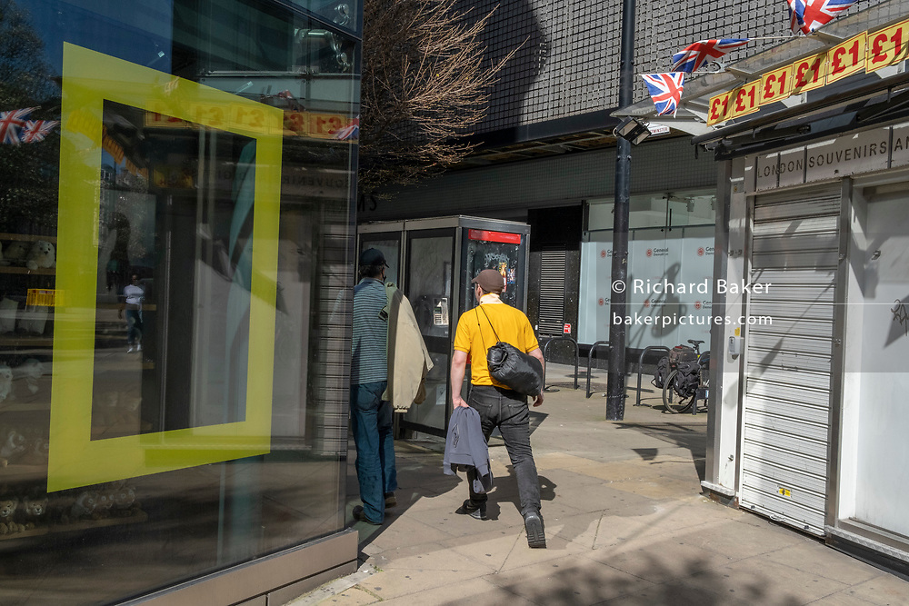Londoners walk past the Disney shop in Oxford Street, where the yellow border frame for National Geographic is in one window, on 29th March 2021, in London, England.