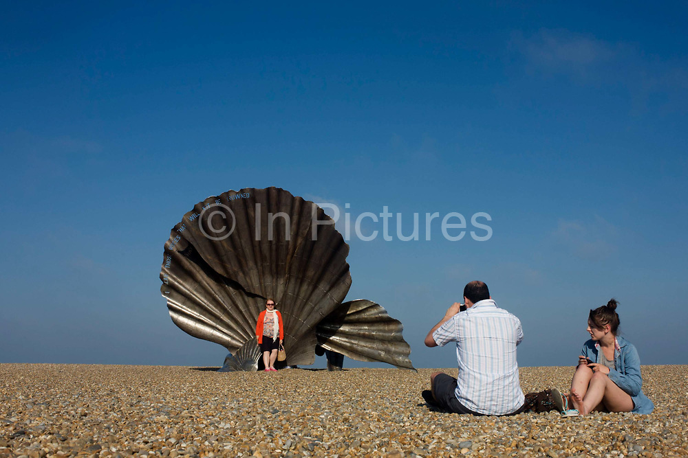"""Families admire Scallop, a 4 metre high steel sculpture of two interlocking scallop shells on Aldeburgh beach dedicated to Benjamin Britten. Hambling's Scallop (2003) stands on the north end of Aldeburgh beach. It is a tribute to Benjamin Britten and is pierced with the words """"I hear those voices that will not be drowned"""" from his opera Peter Grimes. Aldeburgh is a coastal town in Suffolk, East Anglia, England. Located on the River Alde, the town is notable for its internationally renowned Aldeburgh Festival of arts, which takes place at nearby Snape Maltings, was created in 1948 by the resident and acclaimed composer Benjamin Britten. The Blue Flag shingle beach and fisherman huts is where freshly caught fish are sold daily."""