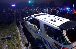 CMPD officers form a line near one of the departments vehicles that was vandalized during a protest on Old Concord Rd. on Tuesday night, Sept. 20, 2016 in Charlotte, N.C. The protest began on Old Concord Road at Bonnie Lane, where a Charlotte-Mecklenburg police officer fatally shot a man in the parking lot of The Village at College Downs apartment complex Tuesday afternoon. The man who died was identified late Tuesday as Keith Scott, 43, and the officer who fired the fatal shot was CMPD Officer Brentley Vinson. Photo by Jeff Siner/Charlotte Observer/TNS/ABACAPRESS.COM