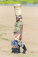 Mozambican lady carrying her clothes washing on her head, Limpopo floodplain, Maputo Province, Mozambique