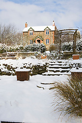 View up steps towards the house in snow.