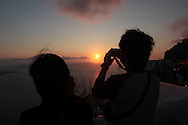 Photographing a sunset on the island of Santorini.  Photograph by Dennis Brack