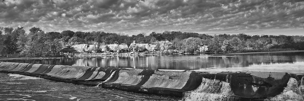 """Sunlight spotlights homes along the Fox River near the Challenge Dam in Batavia, Illinois. The sky is filled with interesting """"popcorn-like"""" clouds."""