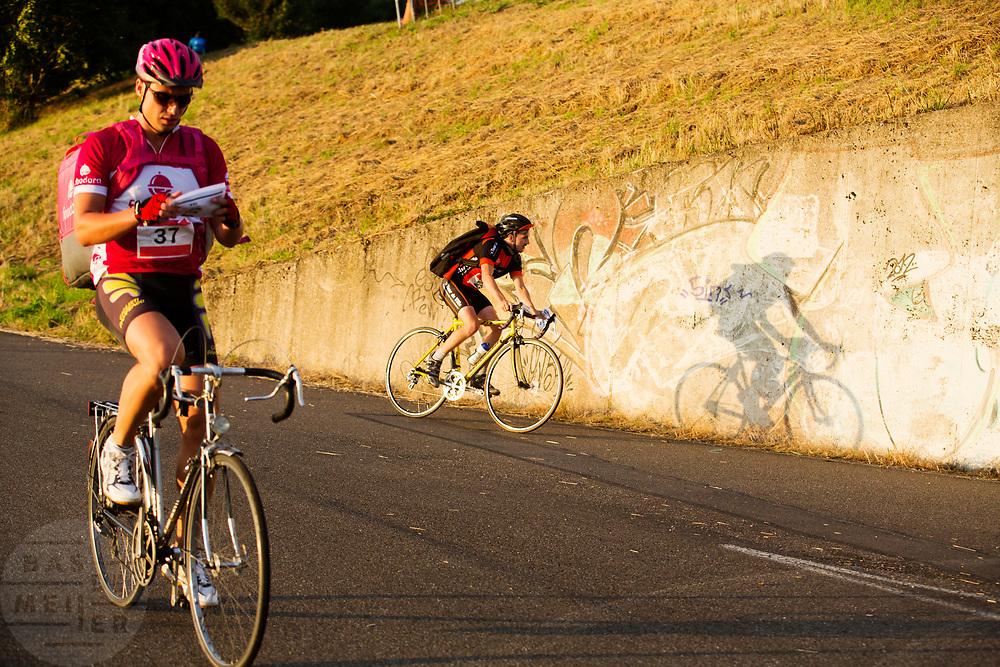 Al rijdend bekijkt een koerier zijn manifest. In Nieuwegein wordt het NK Fietskoerieren gehouden. Fietskoeriers uit Nederland strijden om de titel door op een parcours het snelst zoveel mogelijk stempels te halen en lading weg te brengen. Daarbij moeten ze een slimme route kiezen.<br /> <br /> A messenger is looking at his manifest while riding. In Nieuwegein bike messengers battle for the Open Dutch Bicycle Messenger Championship.