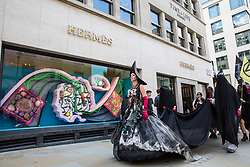 London, UK. 2 July, 2019. Climate change activists from Extinction Rebellion Art and Culture pass along New Bond Street during a silent procession to visit the offices of five major oil companies - ENI, CNPC, Saudi Aramco, Repsol and BP - in order to declare them as crime scenes.
