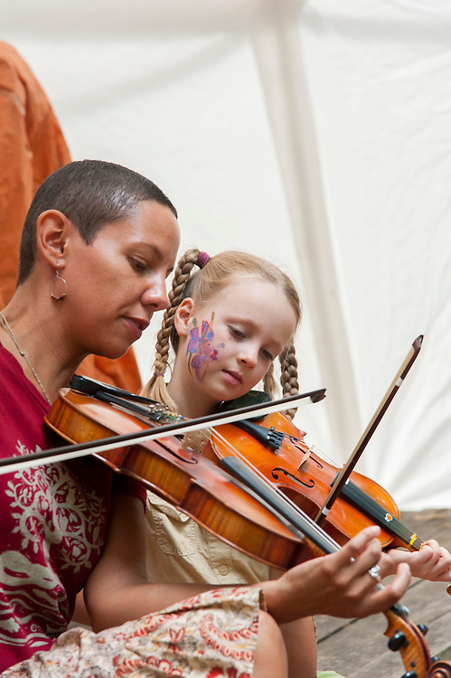Musician Michele Venegas takes time to help young Malia Kirk during an instrument workshop at Blissfest a Michigan music festival.
