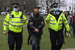 © Licensed to London News Pictures. 06/03/2021. London, UK. An anti-vaccination and anti-lockdown protester is arrested by police officers at a demonstration organised by Jam For Freedom in Richmond.  The group is using music to create positive effects and health against the current tier regulations and anti-vaccination for the Covid-19 disease. Photo credit: Ray Tang/LNP