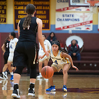 Zuni's Kaitlin Romancito (4) keeps her eye on Hatch Valley's Tavyn Trujillo (14) as she brings the ball down the court in Saturday's championship game between the teams in the Rehoboth Christian High School girls basketball tournament in Rehoboth.