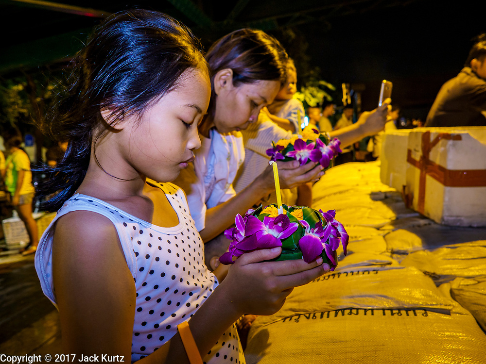 """03 NOVEMBER 2017 - BANGKOK, THAILAND:  A girl prays before floating a krathong during Loi Krathong near Wat Prayurawongsawat on the Thonburi side of the Chao Phraya River. Loi Krathong is translated as """"to float (Loi) a basket (Krathong)"""", and comes from the tradition of making krathong or buoyant, decorated baskets, which are then floated on a river to make merit. On the night of the full moon of the 12th lunar month (usually November), Thais launch their krathong on a river, canal or a pond, making a wish as they do so. Loi Krathong is also celebrated in other Theravada Buddhist countries like Myanmar, where it is called the Tazaungdaing Festival, and Cambodia, where it is called Bon Om Tuk.    PHOTO BY JACK KURTZ"""