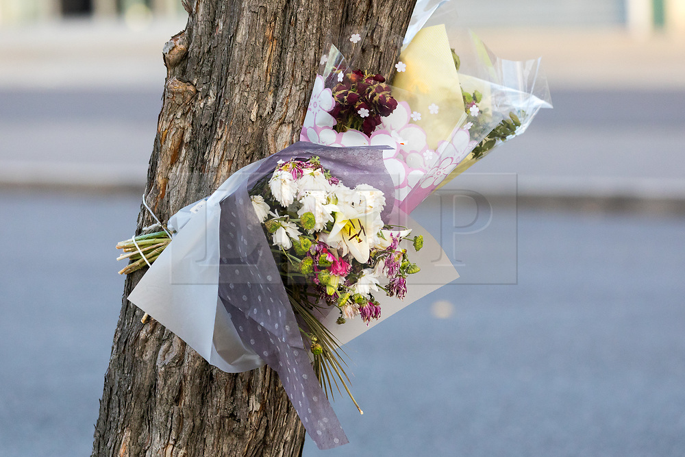 © Licensed to London News Pictures. 13/10/2018. London, UK.  Flowers seen tied to a tree within the crime scene police cordon at Manford Way in Hainault, where police were called at approximately 10:20pm last night to reports of two men stabbed in Manford Way, Hainault and one man, believed aged 23, was pronounced dead at the scene. The second man, believed aged 22, was taken to an east London hospital for treatment where he remains in a critical condition..  Photo credit: Vickie Flores/LNP