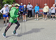 Augusta, New Jersey - A runner in the 72-hour race passes a group of runners waiting to start the 48-hour event during the 3 Days at the Fair races at Sussex County Fairgrounds on May 11, 2012.