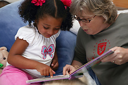 Young girl reading with her Grandmother,