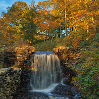 Moore State Park in Paxton is a peaceful retreat in the heart of central Massachusetts. This photo includes the waterfall upstream of the historic Sawmill landmark. Image was taken on a beautiful autumn late afternoon when New England fall color was at peak and the sky featured a great mixture of blue sky and clouds.<br />