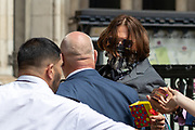 American actor Johnny Depp receives a greeting gift from his supporters as he arrives at the High Court in London on Thursday, July 23, 2020 - to attend the hearing of his legal dispute with UK tabloid newspaper The Sun over allegations he assaulted his former wife Amber Heard. (VXP Photo/ Vudi Xhymshiti)
