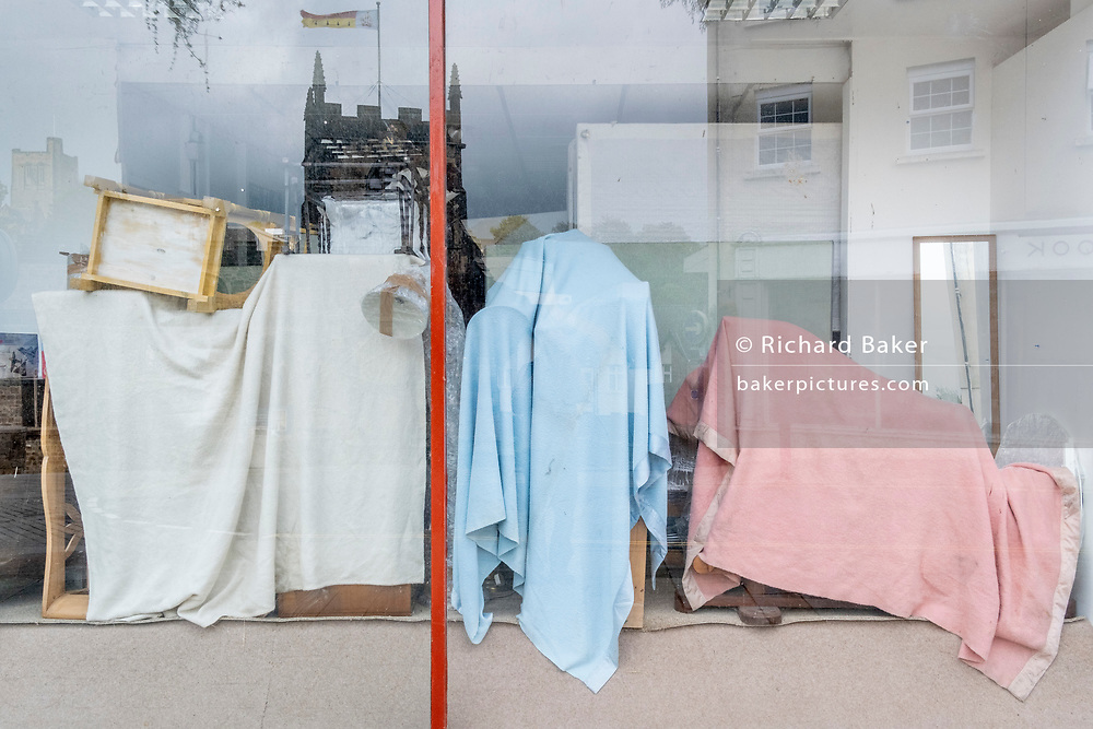 With the reflection of Bangor Cathedral, blankets cover furniture in the window of a high street retailer, on 3rd October 2021, in Bangor, Gwynedd, Wales.