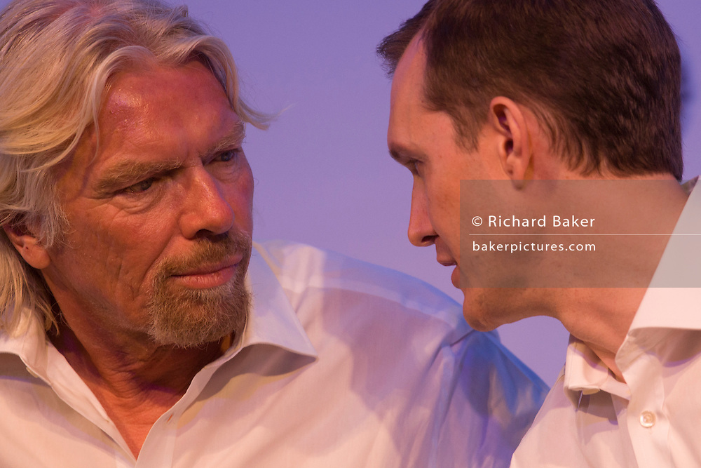Sir Richard Branson consiults with Virgin Galactic CEO George Whitesides during new space tourism presentation.