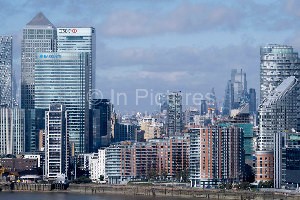 Thames riverside residential properties and the London Docklands cityscape, on 11th August 2021, in London, England.