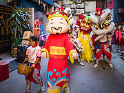 27 JANUARY 2017 - BANGKOK, THAILAND: Chinese lion dancers walk through a neighborhood  on their way to a Chinese New Year performance in Bangkok. 2017 is the Year of the Rooster in the Chinese zodiac. This year's Lunar New Year festivities in Bangkok were toned down because many people are still mourning the death Bhumibol Adulyadej, the Late King of Thailand, who died on Oct 13, 2016. Chinese New Year is widely celebrated in Thailand, because ethnic Chinese are about 15% of the Thai population.    PHOTO BY JACK KURTZ