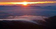 Looking SW from the Mount Tahoma Trails High Hut - the setting sun shines through a gap in the cloud layer lighting a cloud in the foreground streaming over a ridge. Washington state, USA