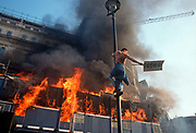 Several metres above the ground, a lone protester hangs on to a street light pole near Londons Trafalgar Square at the height of the Poll Tax Riot on 31st March 1990, in Westminster, London, England. Angry crowds, demonstrating against Margaret Thatchers local authority tax, stormed the Whitehall area and then Londons West End, starting fires and overturning cars, looting stores up Charing Cross Road and St Martins Lane. The anti-poll tax rally in central London erupted into the worst riots seen in the city for a century. Forty-five police officers were among the 113 people injured as well as 20 police horses. 340 people were arrested.