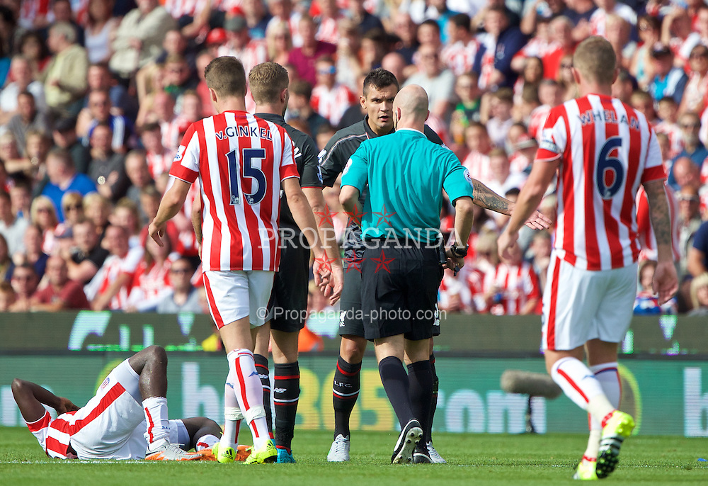 STOKE-ON-TRENT, ENGLAND - Sunday, August 9, 2015: Liverpool's Dejan Lovren looks surprised after being shown a yellow card for a challenge with Stoke City's Mame Diram Diouf during the Premier League match at the Britannia Stadium. (Pic by David Rawcliffe/Propaganda)