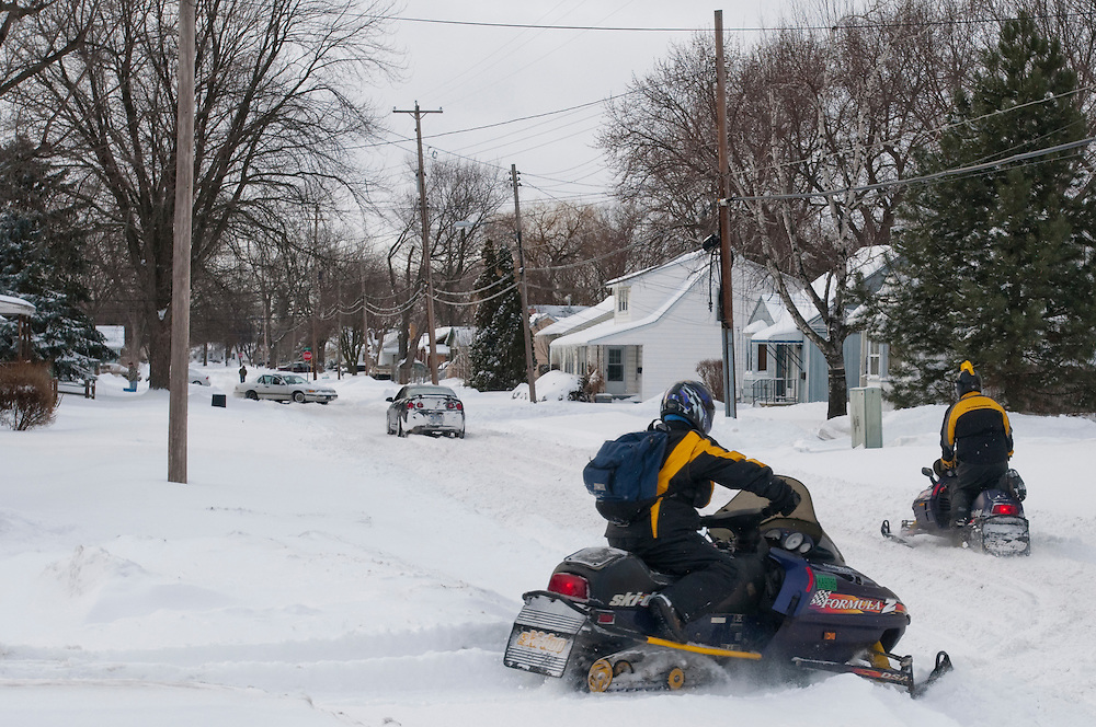 """Matt Dixon   The Flint Journal..From left: Kate and Brandon Lawson hit the road on their snowmobiles after gassing up near Fenton Road and Atherton Road. """"I usually have to go up north to do this,"""" said Brandon. The two had the day off from work due to the weather and were headed toward Swartz Creek."""