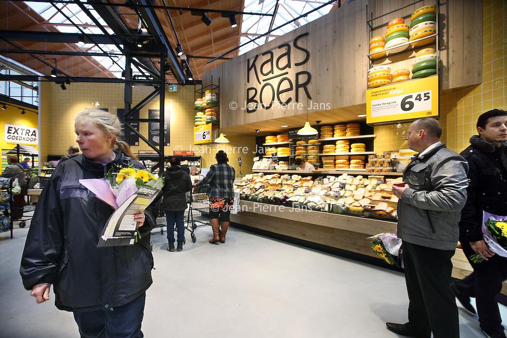 Nederland, Amsterdam , 26 november 2014.<br /> Opening Foodmarkt van Jumbo in amsterdam Noord.<br /> Op 26 november gaat de grootste Jumbo van Amsterdam open. Niet alleen de omvang van de winkel (waarschijnlijk zo'n 2600 m2 ), ook de locatie is speciaal. De enorme foodmarkt zit in een oude loods op het voormalige Storkterrein, een van de meest creatieve plekken van Amsterdam. Hoe groot de foodmarkt precies is, hoe hij eruit gaat zien en wat er te beleven is, houden ze bij Jumbo nog geheim.Wel is duidelijk dat er vanaf woensdag in deze industriële loods zal worden gekokkereld in meerdere foodmarktkeukens 'door koks en andere vakspecialisten'.En dat de producten van Jumbo gezond, lekkeren betaalbaar zijn, aldus Jumbo.<br /> Op de foto: De eerste bezoekers van de foodmarket worden verwend met een bloemetje<br /> Foto:Jean-Pierre Jans