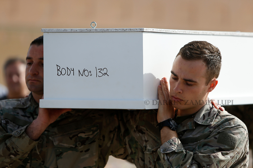 Armed Forces of Malta soldiers carry a coffin with the body of a teenage migrant to an inter-faith burial service at Mater Dei Hospital in Tal-Qroqq, outside Valletta, April 23, 2015. European Union leaders who decided last year to halt the rescue of migrants trying to cross the Mediterranean will reverse their decision on Thursday at a summit hastily convened after nearly 2,000 people died at sea.  Public outrage over the deaths peaked this week after up to 900 migrants died last Sunday when their boat sank on its way to Europe from Libya.<br /> REUTERS/Darrin Zammit Lupi MALTA OUT. NO COMMERCIAL OR EDITORIAL SALES IN MALTA