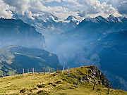 """From Männlichen, look up Lauterbrunnen Valley to Lauterbrunnen Breithorn (3780 meters or 12,402 feet elevation) in the Berner Oberland, Switzerland, the Alps, Europe. The world's longest continuous rack and pinion railway (Wengernalpbahn) goes from Grindelwald up to Kleine Scheidegg and down to Wengen and Lauterbrunnen. A gondola (gondelbahn) connects Grindelwald with Männlichen, where a cable car goes down to Wengen (Luftseilbahn Wengen-Männlichen). The Bernese Highlands are the upper part of Bern Canton. UNESCO lists """"Swiss Alps Jungfrau-Aletsch"""" as a World Heritage Area (2001, 2007)."""