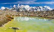 """Bright yellow algae grows in a tarn (mountain pond) which reflects peaks of Dents des Veisivi (left) and Aiguilles de la Tsa (right) above Arolla Valley, part of Val d'Hérens, in Valais (Wallis) Canton, Switzerland, Europe. Hike the High Route (Chamonix-Zermatt Haute Route) for classic mountain scenery. Panorama stitched from 3 images. Published in """"Light Travel: Photography on the Go"""" book by Tom Dempsey 2009, 2010. Published in Ryder-Walker Alpine Adventures """"Inn to Inn Alpine Hiking Adventures"""" Catalog 2006-2009, 2011-12."""