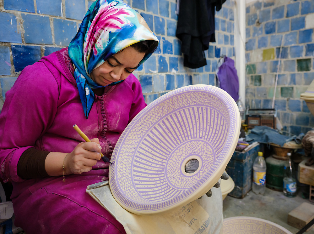 FEZ, MOROCCO - CIRCA APRIL 2017:  Moroccan artisan woman painting a ceramic plate in a gift shop