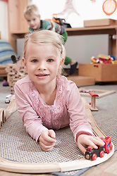 Portrait of little girl playing with wooden railroad in her kindergarten