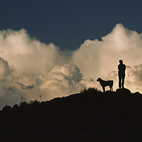 Woman and dog explore volcanic tablelands under summer thunderheads.